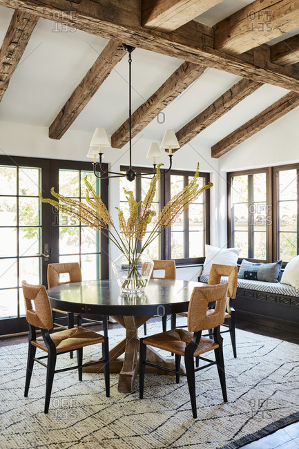 September 30, 2020 - Rustic wood beams on ceiling over a large round dining room table in a room with large windows
