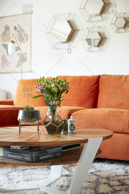 October 19, 2020 - Plants on a coffee table in front of an orange velvet sofa in a beautiful modern home