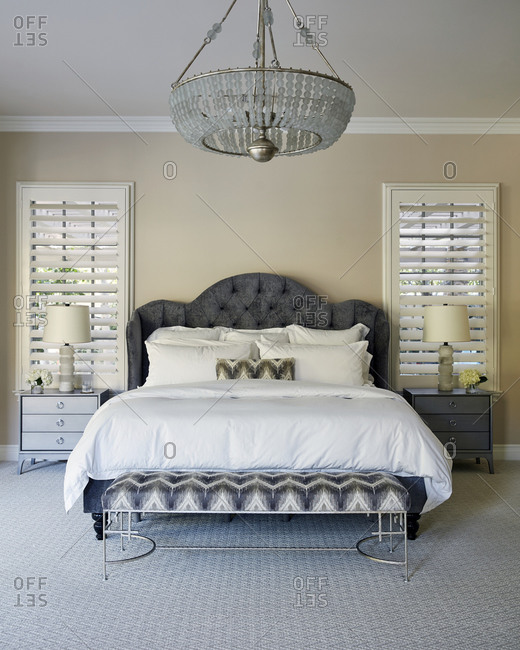 Beautiful chandelier above a large bed in the master bedroom of a modern home