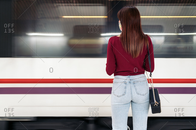 Young caucasian woman waiting for a train and wearing a face mask in Madrid, Spain
