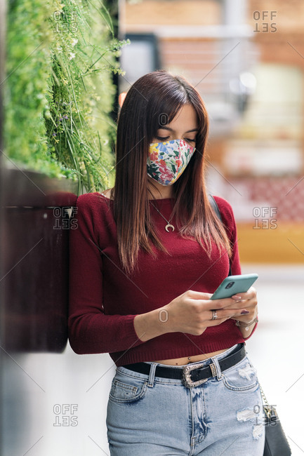 Young caucasian woman using her smartphone outside a train station, wearing a medical mask