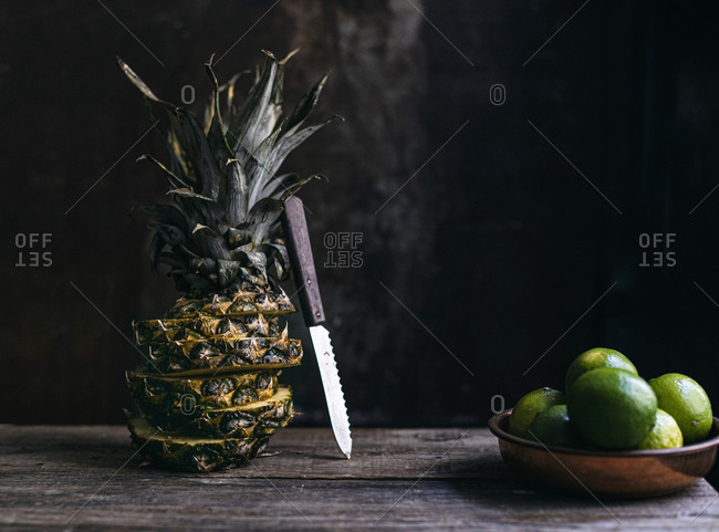 Sliced whole pineapple and limes in a copper dish