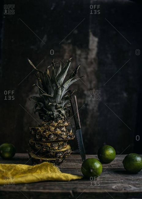 Sliced and limes arranged pineapple on a wooden table