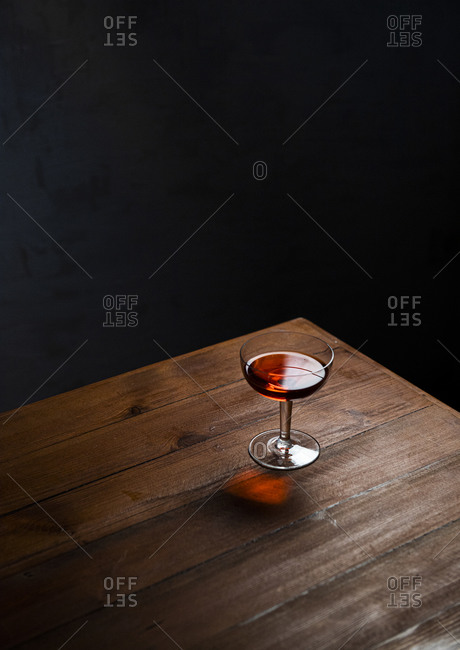 A red alcoholic drink in a coupe glass in a dark setting