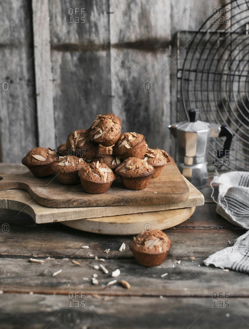 Pile of almond muffins on cutting board in a rustic setting