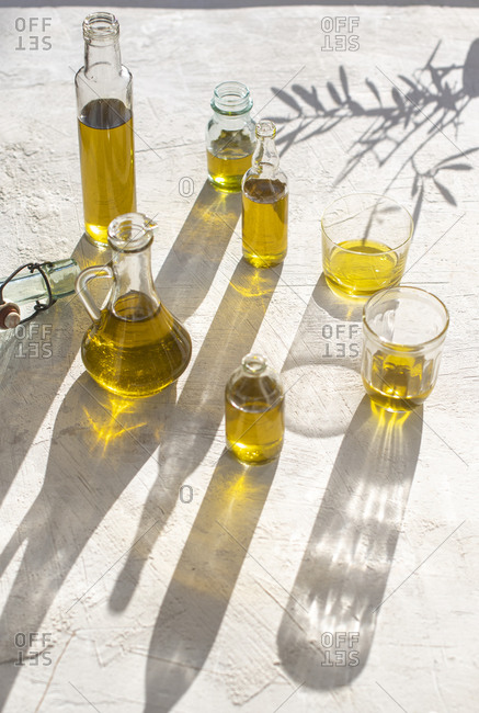 Bottles of olive oil on light surface in the sun