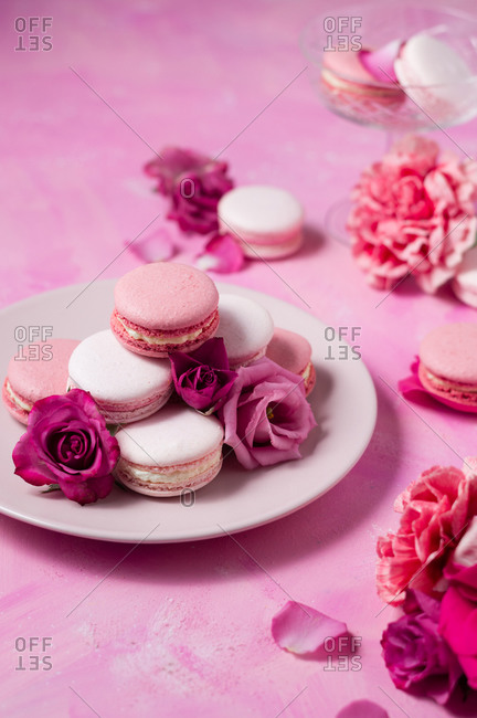 Pink macarons served on a plate with flowers around