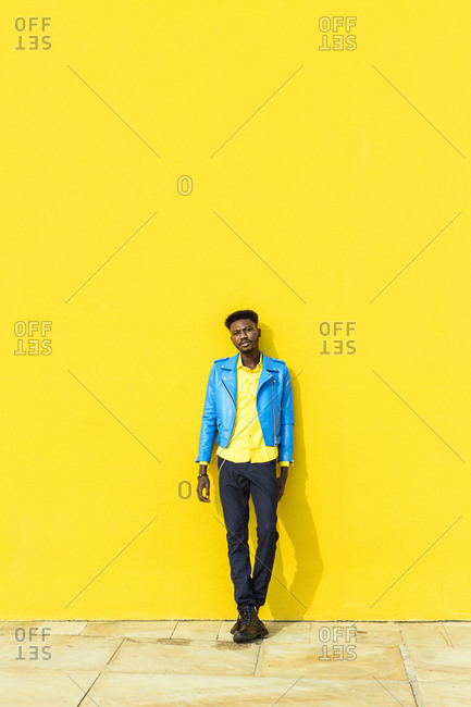Confident African American man standing against a yellow wall on sunny day