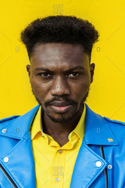 Isolated African American man standing against a yellow wall on sunny day