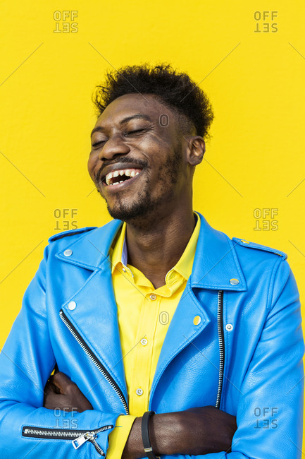 Smiling African American man with eyes closed standing against yellow wall