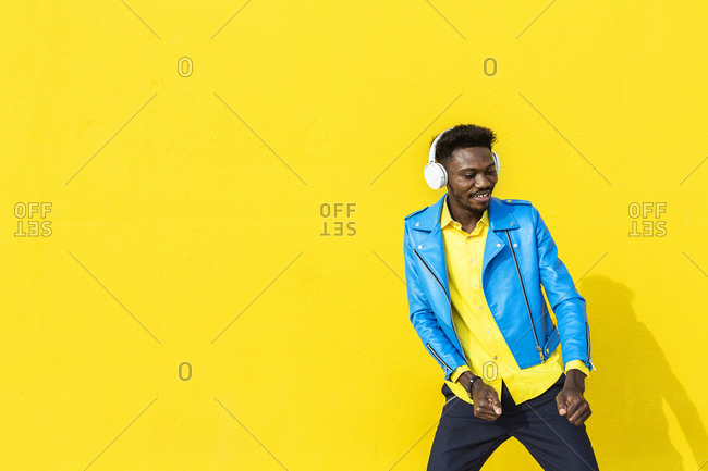 African American man dancing outdoors while listening to music against yellow background