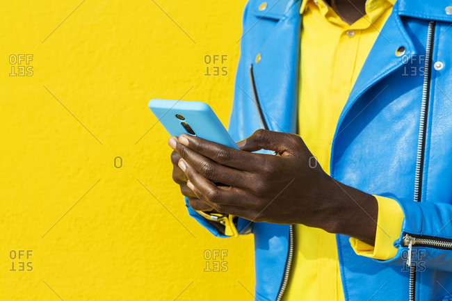 Unrecognizable man in blue jacket using cell phone in front of yellow wall