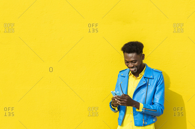Happy man in blue jacket using smartphone in front of yellow wall
