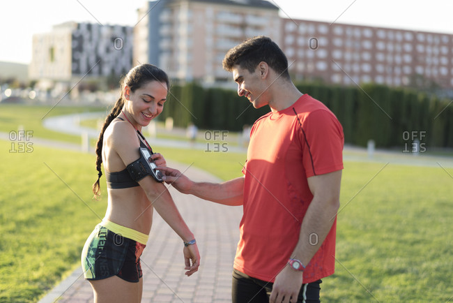 Two runners training outdoors and checking woman's smartphone