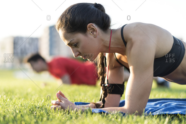 Two athletes doing push ups in a city park