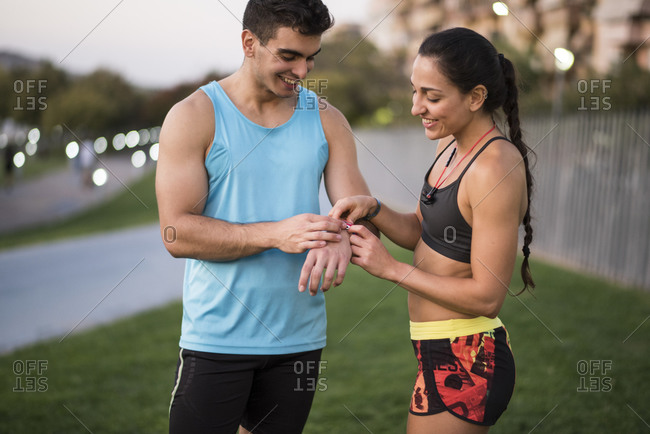 Young couple looking at sports watch to check their running stats