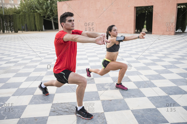 Attractive fitness couple stretching arms and legs in public park after running