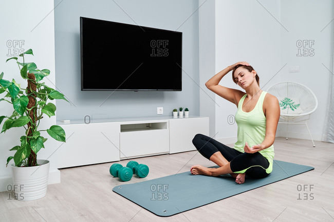 Fit female sitting on mat and doing stretching exercises while warming up before workout at home