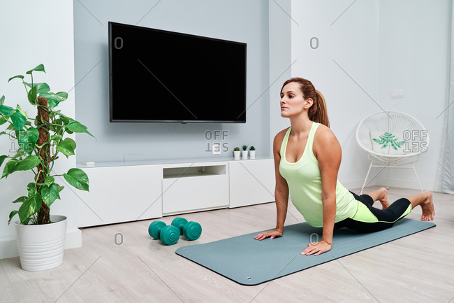 Slim focused female stretching body and doing yoga in Bhujangasana while doing yoga on mat at home