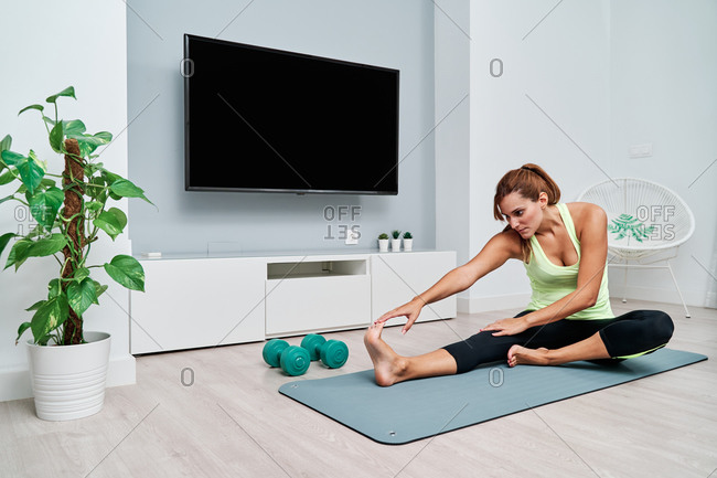 Fit female sitting on mat and doing forward bend exercise while warming up before workout and stretching body at home