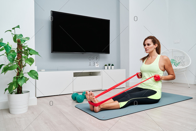 Side view of fit female athlete sitting on mat and doing exercises with elastic band while pumping arm muscles during workout at home