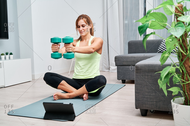 Determined sportswoman sitting on mat and exercising with dumbbells while watching online video on tablet during training