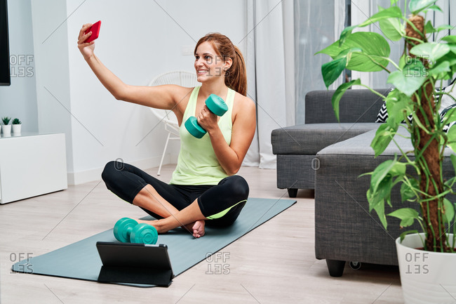 Determined sportswoman sitting on mat taking selfie with mobile phone while resting from exercising with dumbbells watching online video on tablet during training