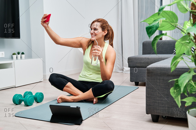 Delighted fit female athlete drinking water after training and taking selfie on smartphone after home workout