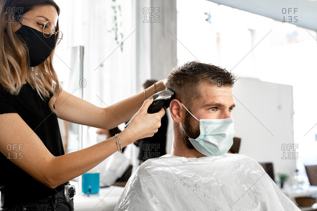 Side view of female master with trimmer cutting hair of male customer in protective mask during grooming procedure in salon at coronavirus pandemic time