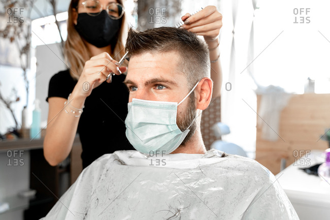 Female master with scissors cutting hair of male customer in protective mask during grooming procedure in salon at coronavirus pandemic time