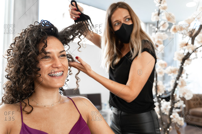 Professional hairdresser in black protective mask using hair comb while making hairdo to long haired female customer in salon