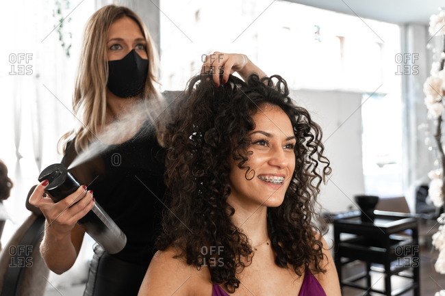 Hairstylist in protective mask fixing hairdo of happy curly haired female client with hair spray  in modern hairdressing studio