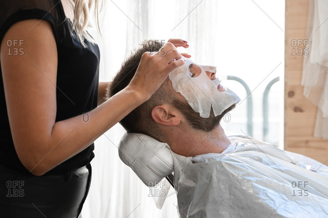 Professional female master in protective mask applying moisturizing facial mask to relaxed bearded male customer during grooming procedure in salon