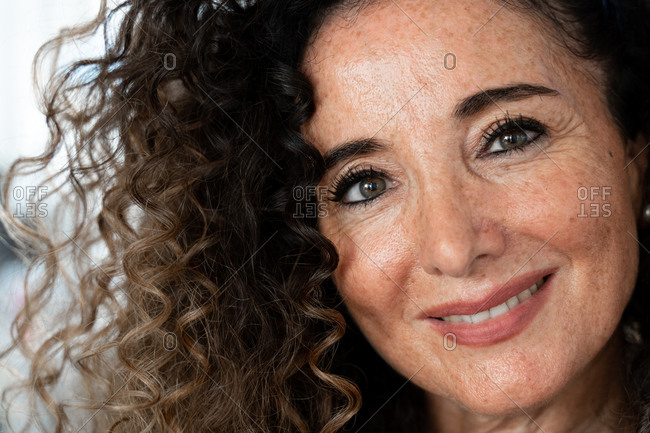 Attractive smiling middle aged freckled brunette with long curly hair and casual makeup