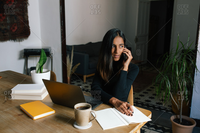 Busy ethnic female entrepreneur sitting at table in home office and speaking on cellphone about new startup project while working remotely and looking away
