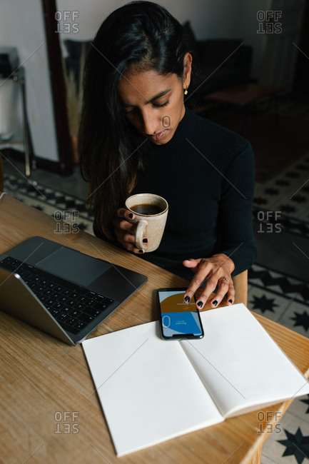 Female sitting at table with cup of coffee and analyzing diagram on smartphone while working on online project