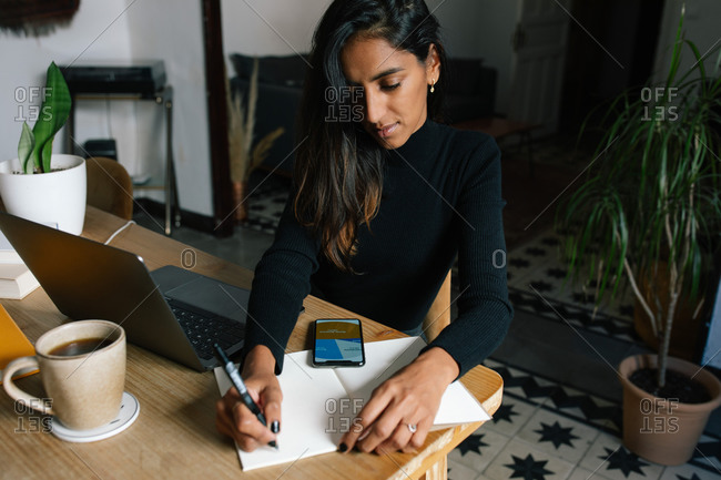 High angle of Indian female entrepreneur sitting at table and writing plans in notebook while working at home in cozy workplace