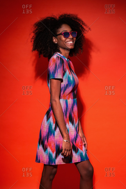 Happy black woman with Afro hairstyle wearing vivid dress with sunglasses and laughing against red background