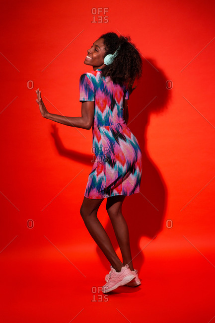 Full body side view of black woman with Afro hairstyle wearing vivid dress with pink sneakers standing on red background