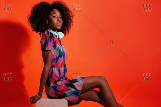 Full body side view of black woman with Afro hairstyle wearing vivid dress with pink sneakers sitting on red background