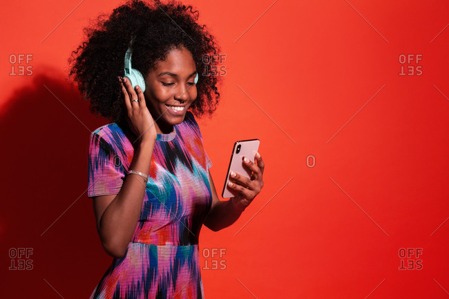 Bright Cuban model with Afro hairstyle listening to music with headphones and browsing smartphone on red background