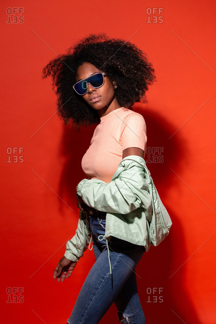 Modern black woman with Afro hairstyle wearing fashionable sunglasses with jacket on red background