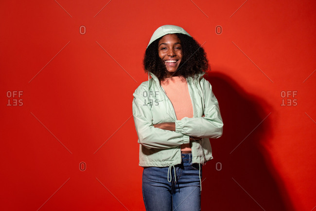 Modern ethnic woman with Afro hairstyle wearing casual denim with jacket and hood on vivid red background