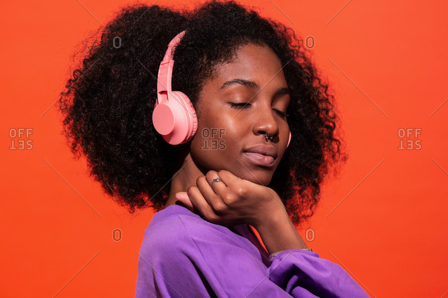 Modern unemotional black woman with Afro hairstyle wearing pink headphones and listening to music on red background