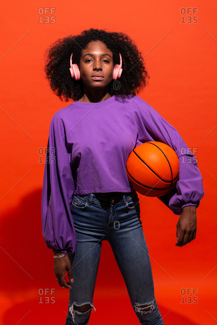 Modern unemotional black woman with Afro hairstyle wearing pink headphones and holding orange basketball and listening to music on red background
