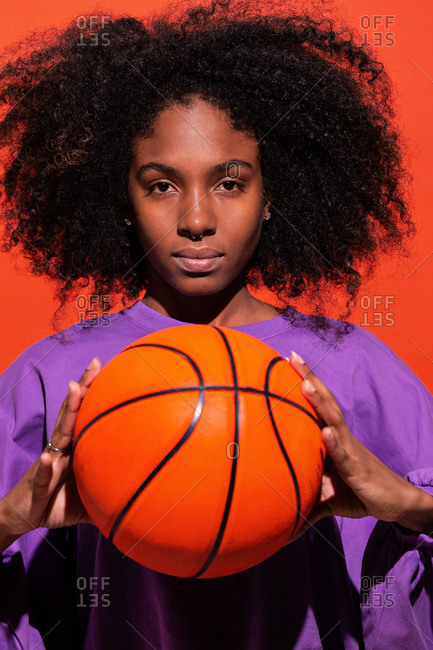 Emotionless ethnic woman with Afro hair wearing purple sport shirt and holding bright orange basketball in studio