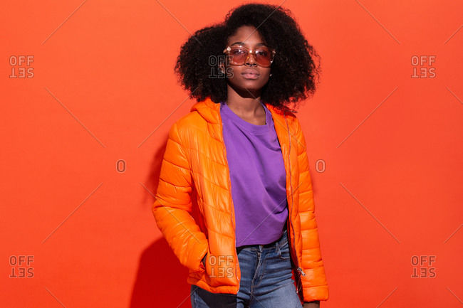 Young black female in purple shirt with denim and orange jacket standing with hands in pockets on red background looking at camera