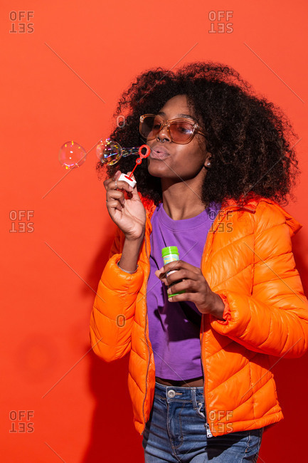Modern African American female in colorful jacket blowing soap bubbles having fun in studio on red background