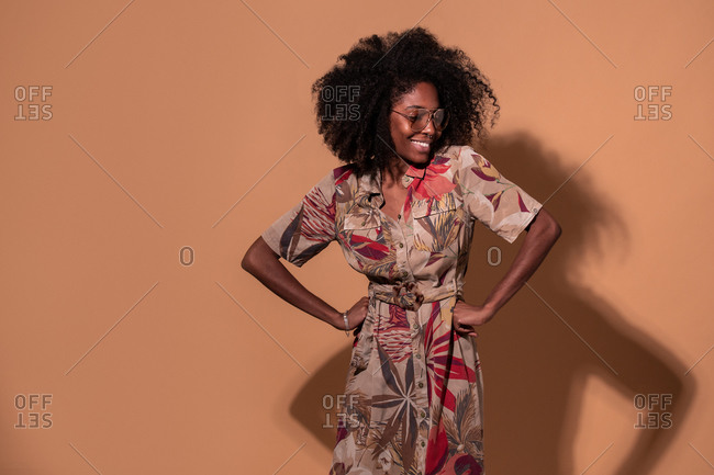 Happy Cuban female in trendy dress and glasses standing with hands on waist on brown background
