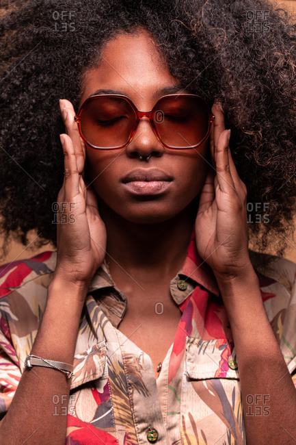 Confident Cuban woman with Afro hairstyle wearing sunglasses with floral shirt closing eyes